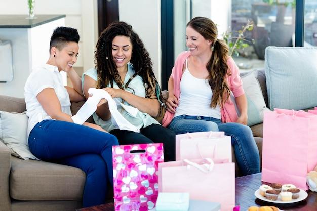ソファに座って、赤ちゃんの服を見ながら笑顔の3人の女性