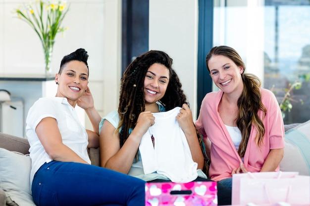ソファに座って、赤ちゃんの服を見ながら笑顔の3人の女性の肖像画