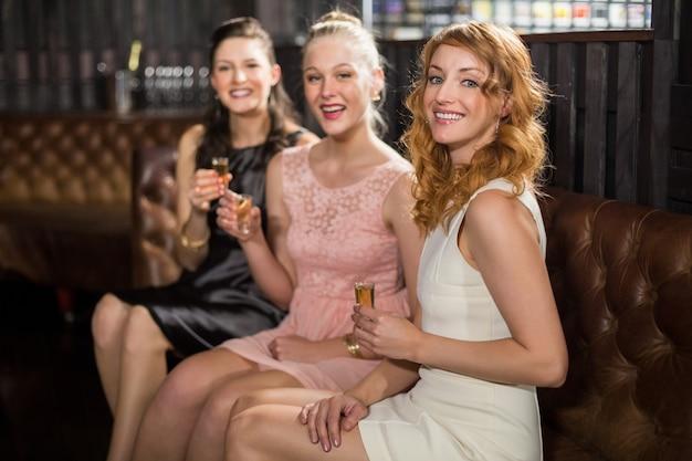 バーでテキーラを持つ3人の女性の友人