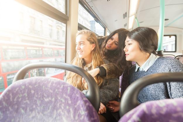 窓から外を見ている3人の女性。バス