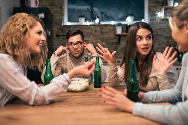 話している3人のガールフレンドを聞いてうんざりして、彼の耳に指を持つ若い男