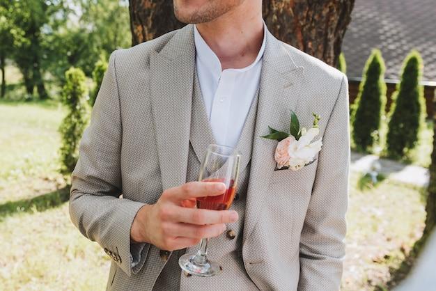結婚式の日にバラスパークリングワインのグラスを保持しているブートニアを着ている3ピースのスーツを着た新郎