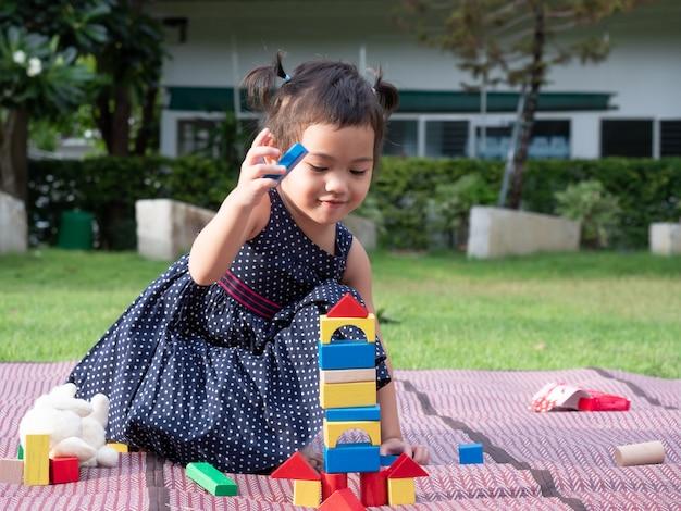 アジアのかわいい女の子3歳の庭でマットの上の木製のブロックを再生します。