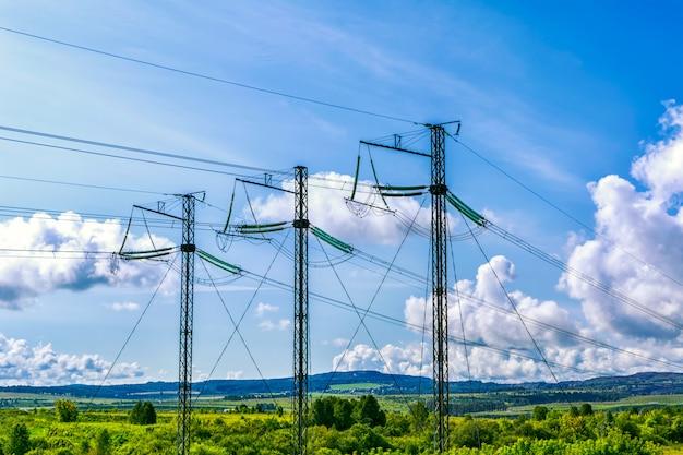 曇り空の上の3つの高電圧送電鉄塔