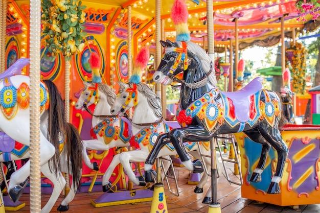 休日の公園で古いフランスのカルーセル。伝統的な見本市会場のビンテージカルーセルに3頭の馬。馬とメリーゴーランド。