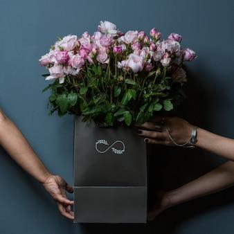 壁にピンクのバラの黒いバスケットを保持している3つの手