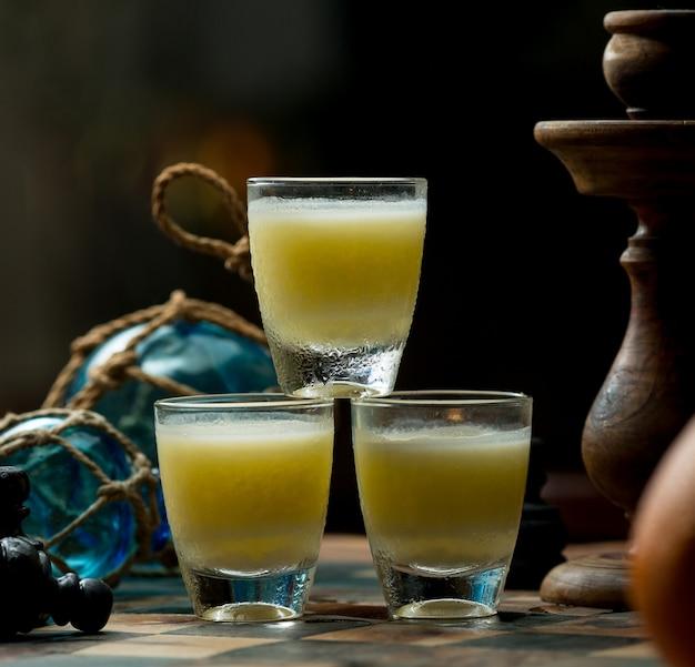 バーのテーブルに立っているアルコール飲料の3つの小さなグラス