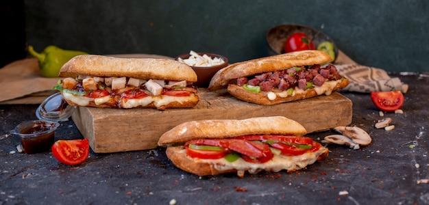 石のテーブルの上にミックスフードが入った3つのさまざまなバゲットサンドイッチ