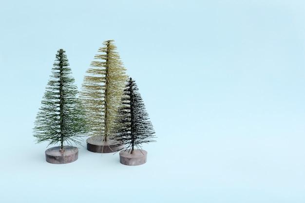 最小限のスタイルで明るい背景に3つのクリスマスツリー。