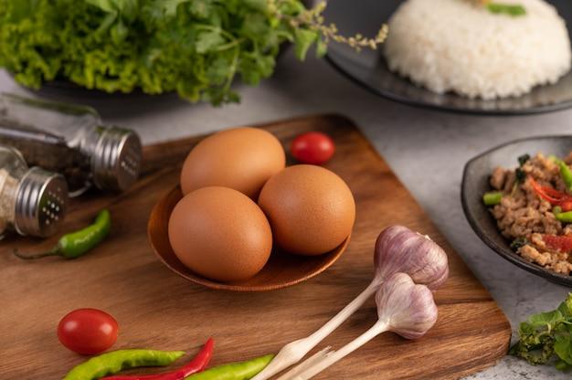 ニンニクトマトと唐辛子の皿の上の3つの鶏の卵。