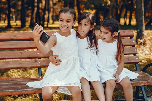 夏の公園に座っている3人の幼い姉妹