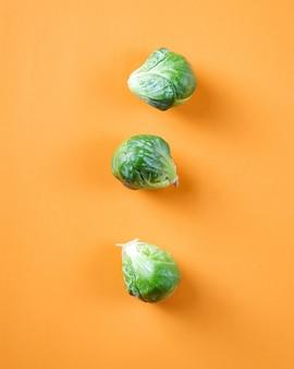 オレンジ色の表面に3つの緑のキャベツ