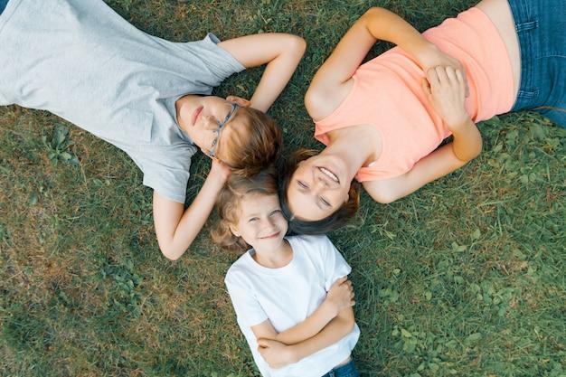 緑の芝生で楽しんでいる3人の子供のフレンドリーな家族