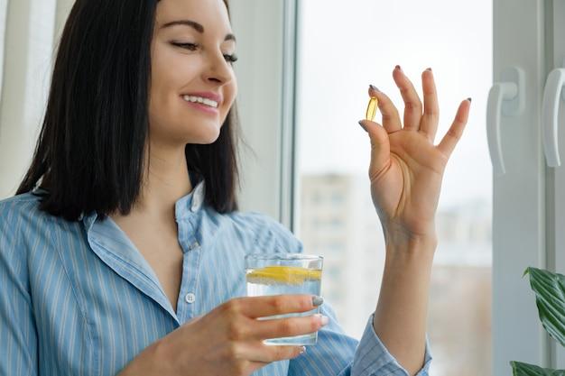 女性はオメガ3とレモンと新鮮な水のガラスを保持している丸薬を取ります