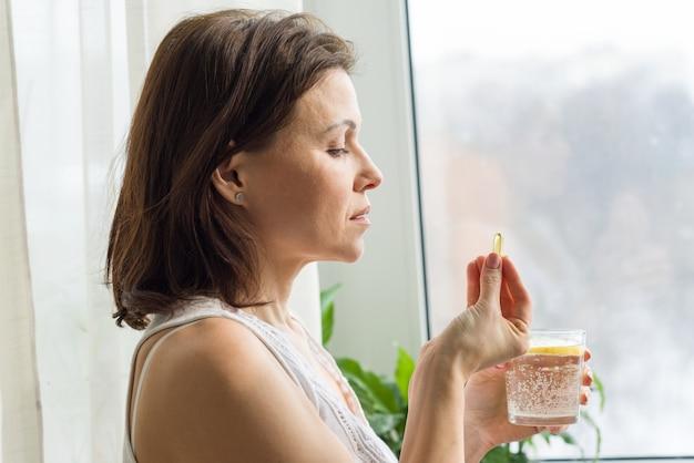 Женщина принимает таблетки с омега-3 и держит стакан свежей воды с лимоном.
