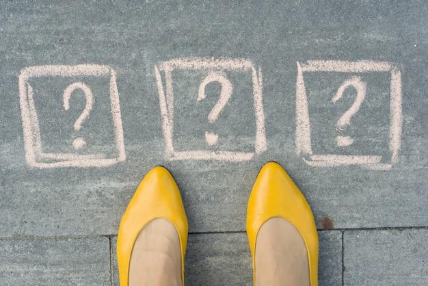 Ноги женщины с 3 вопросительными знаками перед ее ногами, нарисованными на сером тротуаре