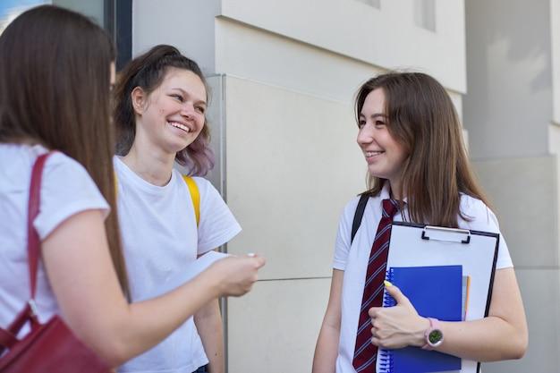 学生の女の子と話す。バックパックの本を持つ3人のティーンエイジャー、屋外の笑いと話。