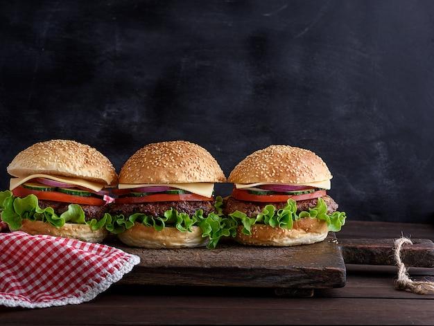 茶色の木の板に野菜と3つのハンバーガー