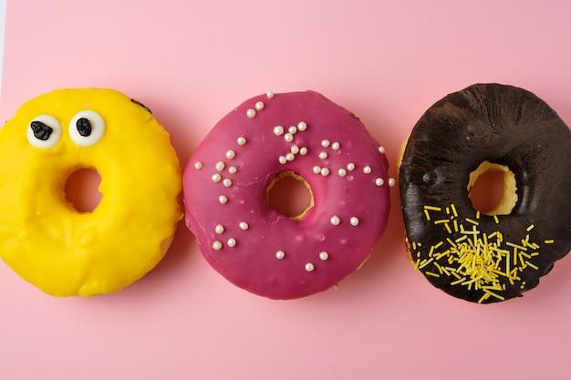 黄色の背景に振りかけると3つのラウンドの異なる甘いドーナツ