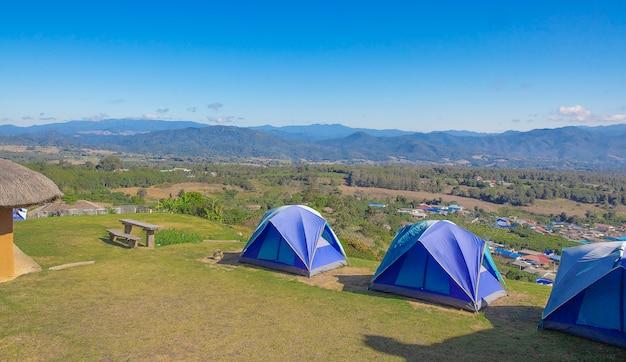 高い丘の上の青の3つのテント。