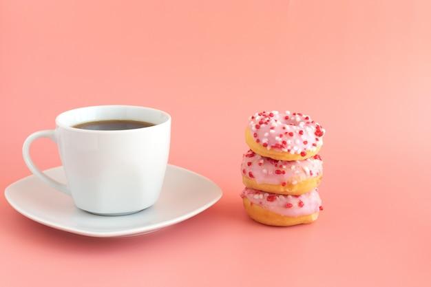 新鮮なブラックコーヒー、エスプレッソ、3つのドーナツ、ピンクのアイシング、ピンクの次のホワイトコーヒーカップ