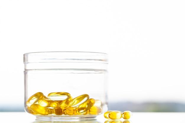 Витаминные добавки, рыбий жир в желтых капсулах омега-3.
