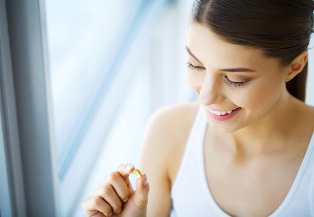 Витамины. здоровое питание. счастливая девушка с омега-3 капсулы рыбьего жира. концепция здорового питания.