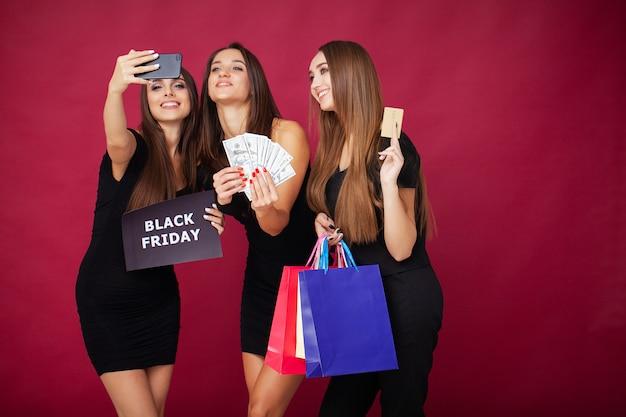 ショッピング。黒い金曜日の休日に赤の空白を割引を保持している3人の女性