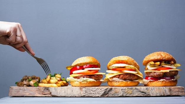 素朴なファーストフードのおいしい料理。ジューシーな3ハンバーガーポテトと灰色の背景にキノコ。フォークで食べる。