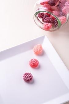 分離した白い背景の上のガラスの瓶にジューシーな果実の形のキャンディー杖お菓子と白いプレート上の3つのキャンディー杖