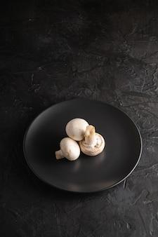 暗い黒のテクスチャ背景、角度ビューコピースペースの黒いプレートに3つのシャンピニオンキノコ健康食品
