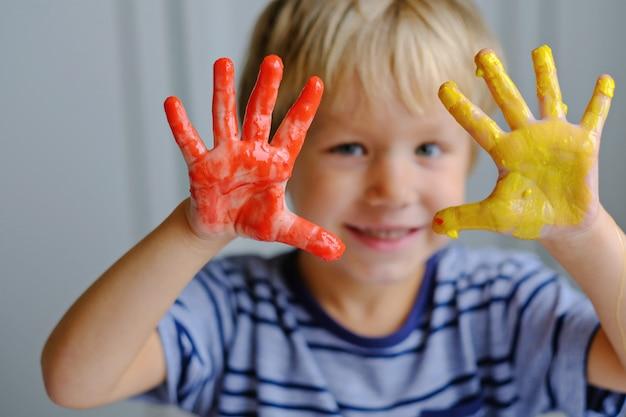 幸せな3歳の男の子の指絵の具を塗る