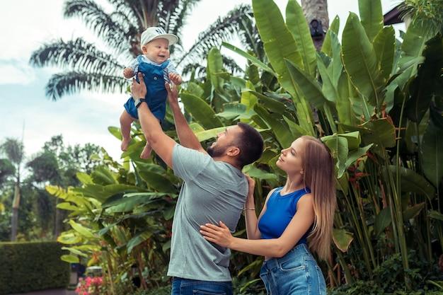 屋外の家族。家族3人が楽しんで、屋外で遊ぶ。幸せな家族 。