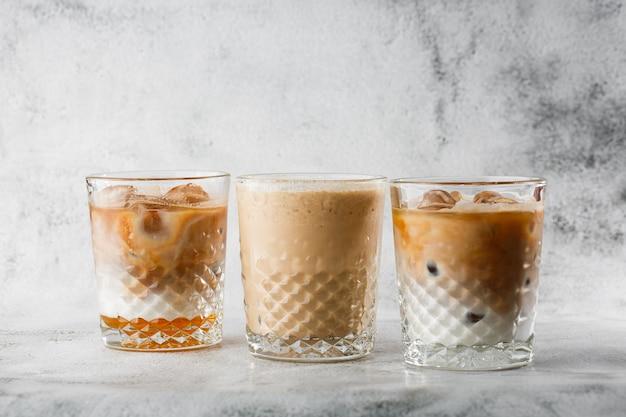 明るい大理石の背景に分離された冷たい醸造コーヒーとミルクとアイスココアの3つのグラス。俯瞰、コピースペース。カフェメニューの宣伝。コーヒーショップメニュー。横の写真。