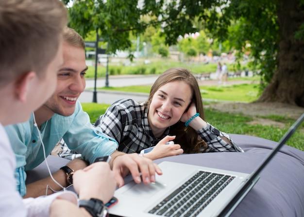 屋外でクッションの上に横たわる3人の若い友人、男は女の子を見ています。