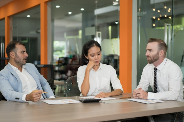 3人の勤勉なビジネスアナリストが机上でダイアグラムを扱う