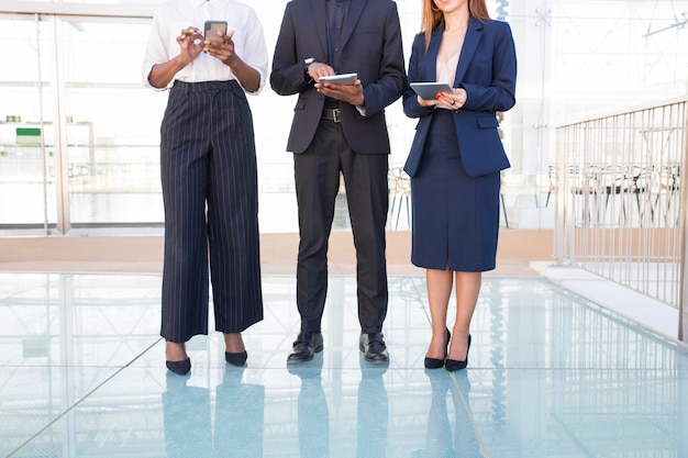 オフィスホールでデジタルデバイスを使用している3人の事業チーム