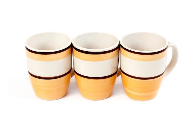 白い表面に分離された3つのマグカップの行