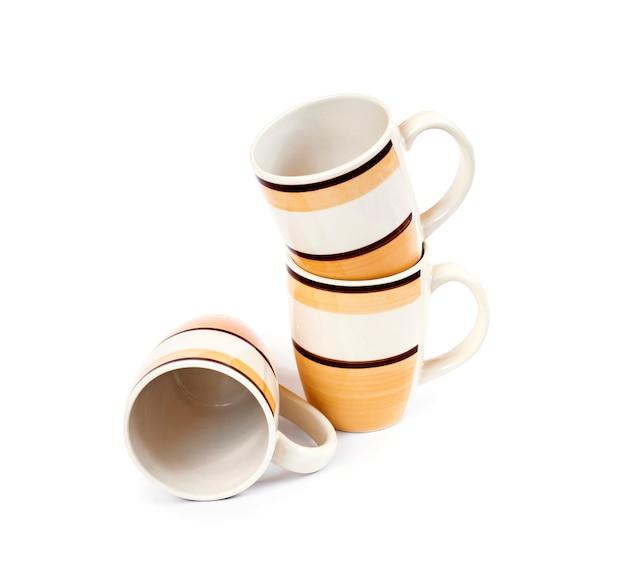白い表面に分離された3つのマグカップのスタック
