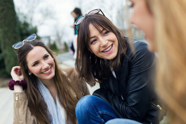 3人の若い女性が通りで笑って話す。