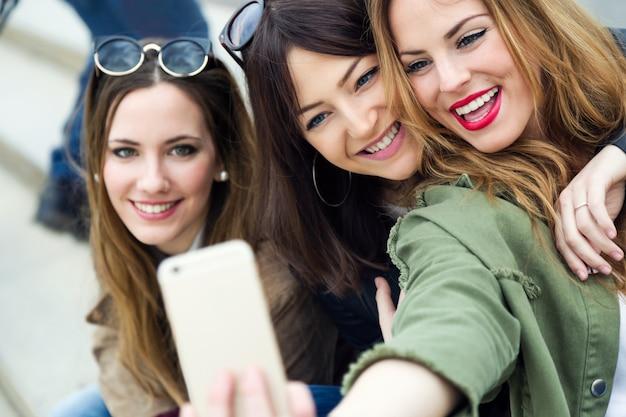 3人の若い女性が通りに携帯電話を使います。