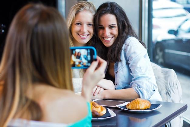 スマートフォンで写真を撮っている3人の友人