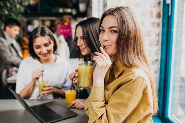 カフェでノートパソコンで試験の準備をする3人の学生