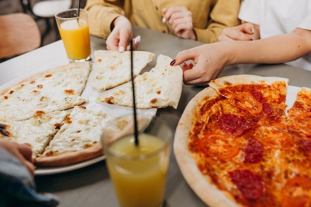 バーでピザを持っている3つのガールフレンド
