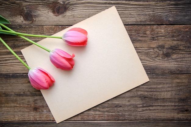 3つのピンクのチューリップと木製のテーブルに紙のシート