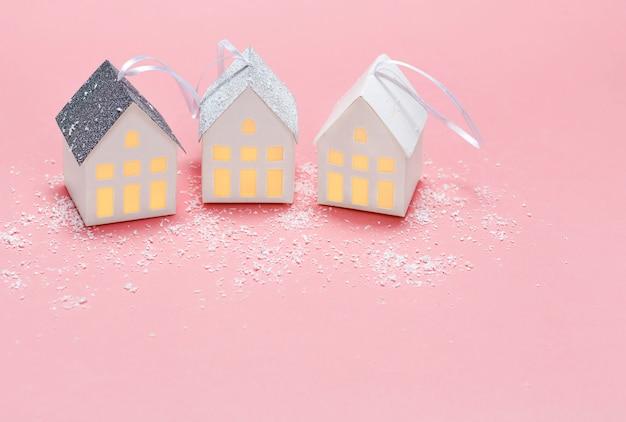 ピンクの背景の3つの紙の白い家。コピースペース。上面図。新年のコンセプト。