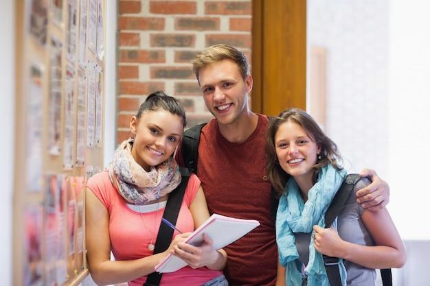 掲示板の横に立つ3人の笑顔の学生