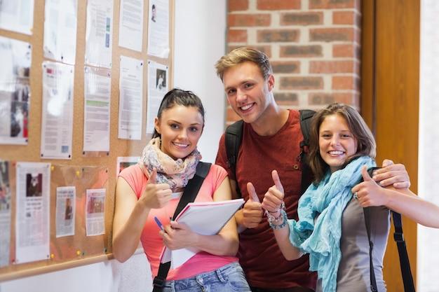 3人の笑い声の学生が親指を掲示する掲示板の隣に立っている