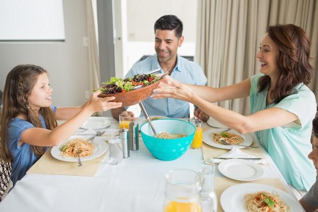 ダイニングテーブルに座っている3人の幸せな家族