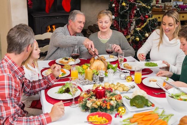 クリスマスディナーを一緒にしている3世代の家族